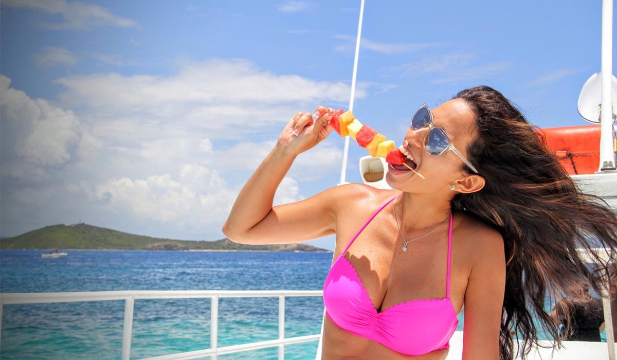 Woman enjoys a fruit kabob on the Fun Cat Catamaran Puerto Rico at Icacos Puerto Rico