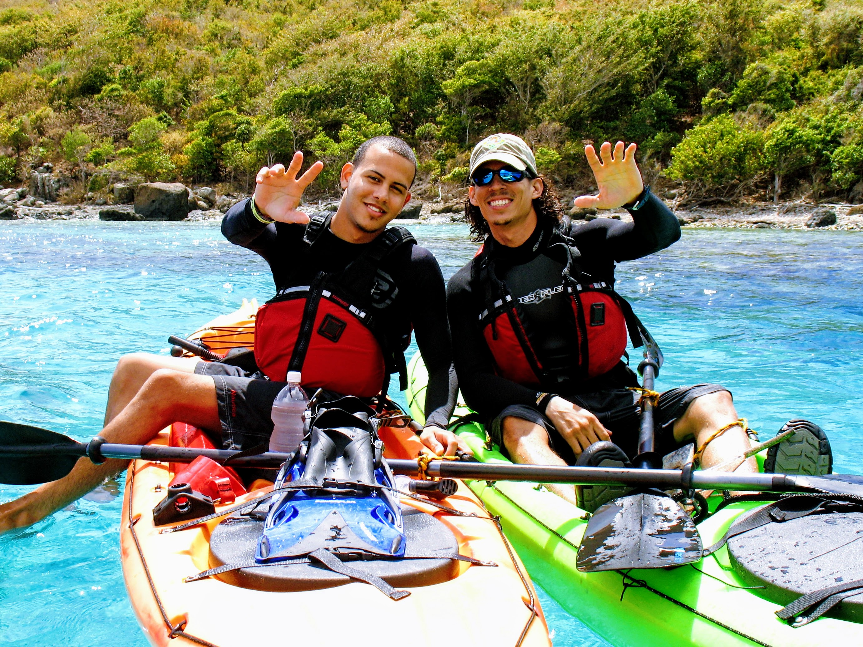 Two men smile and wave from their kayaks before a snorkeling in culebra session with the culebra day trip of kayaking puerto rico