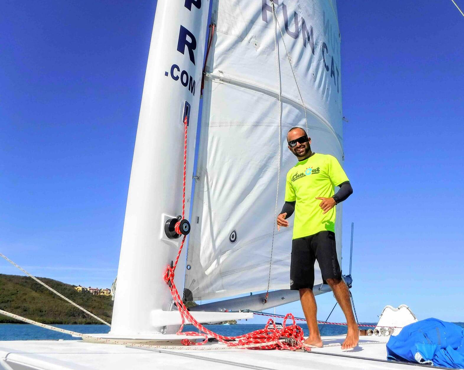 Man smiles next to the sail of the Fun Cat Catamaran Puerto Rico in Icacos Puerto Rico